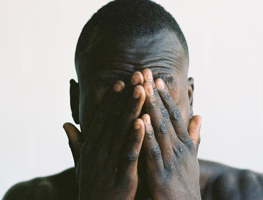 Man with hands over his eyes