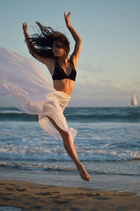 Athletic Woman Jumping on a Beach