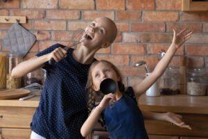 Cancer Survivor and Daughter Singing in a Kitchen