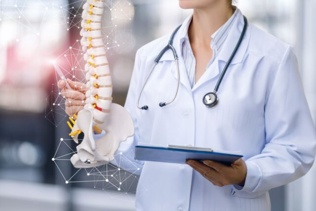 Doctor Standing around a Spine